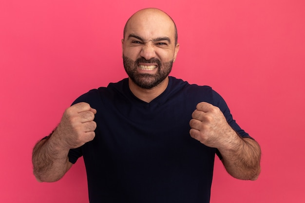 Uomo barbuto in maglietta blu scuro che stringe i pugni con espressione infastidita in piedi sopra il muro rosa