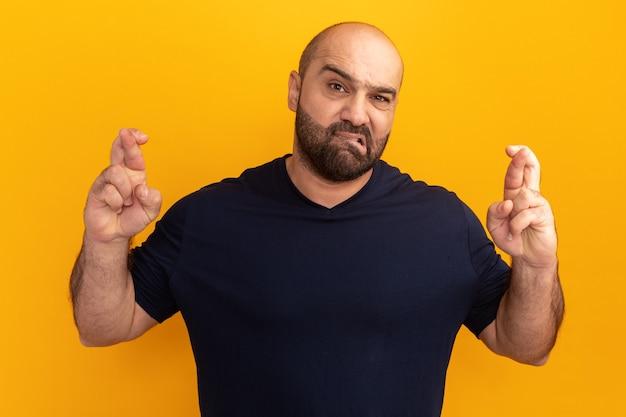 Uomo barbuto in maglietta blu scuro confuso labbro mordace incrocio le dita in piedi sopra la parete arancione