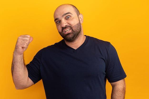 Uomo barbuto in maglietta blu scuro confuso che punta indietro in piedi sopra il muro arancione