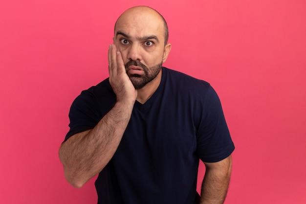 Uomo barbuto in maglietta blu scuro confuso e preoccupato con il braccio sulla guancia in piedi sopra il muro rosa