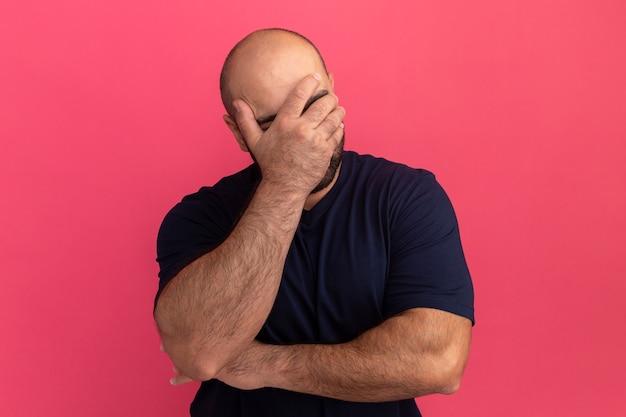 Uomo barbuto in maglietta blu scuro che copre il viso con la mano che sembra annoiato e depresso in piedi sopra il muro rosa