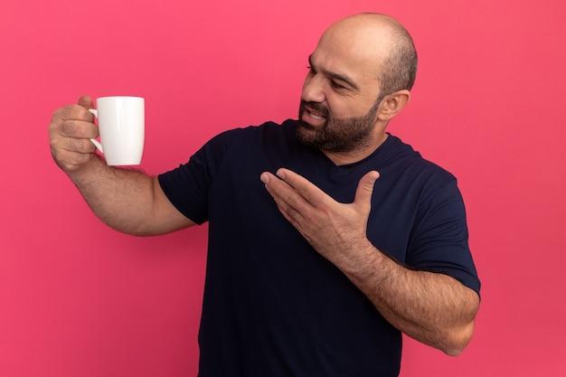 Uomo barbuto in maglietta blu scuro che tiene una tazza che punta con il braccio alla tazza con espressione infastidita in piedi sopra il muro rosa