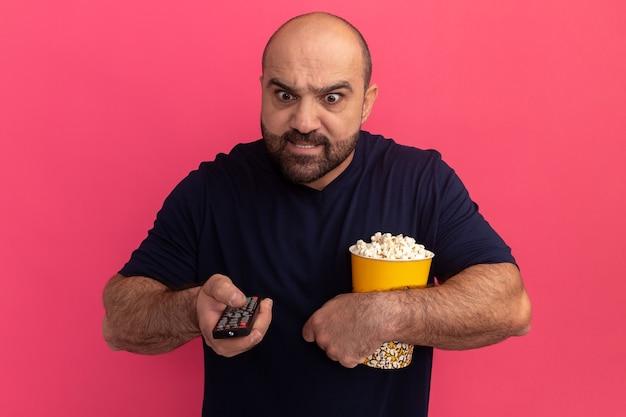 Uomo barbuto in maglietta blu scuro che tiene il secchio della tenuta di popcorn e telecomando della tv che sembra infastidito e irritato in piedi sopra il muro rosa