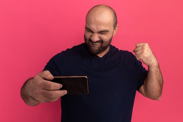 Uomo barbuto in maglietta blu scuro che tiene smartphone guardandolo felice ed eccitato stringendo il pugno in piedi sopra il muro rosa