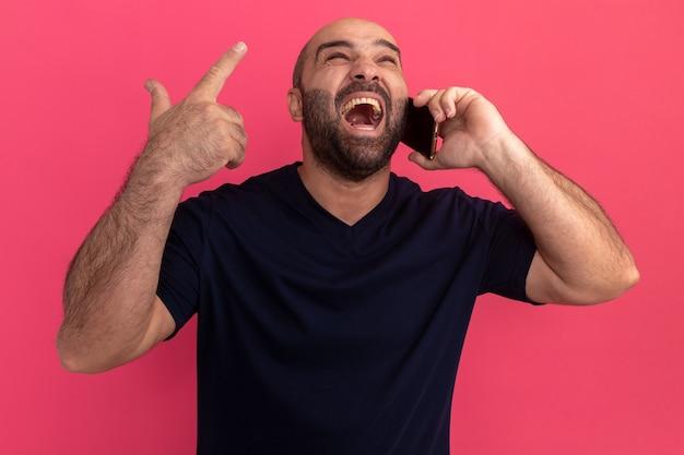 Uomo barbuto in maglietta blu scuro che sembra gridare infastidito impazzire mentre parla al telefono cellulare in piedi sopra il muro rosa