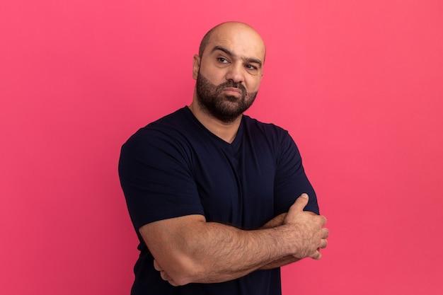 Uomo barbuto in maglietta blu scuro che sembra asdie con le braccia incrociate essendo scontento in piedi sopra il muro rosa