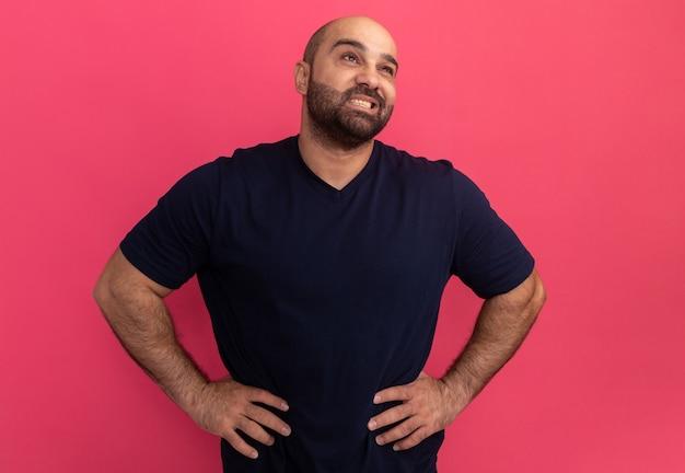 Uomo barbuto in maglietta blu scuro che osserva da parte con il sorriso sul viso con le braccia all'anca in piedi sopra il muro rosa