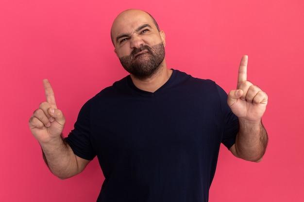 Uomo barbuto in maglietta blu scuro che osserva in su rendendo la bocca ironica con espressione delusa che mostra le dita indice in piedi sopra il muro rosa