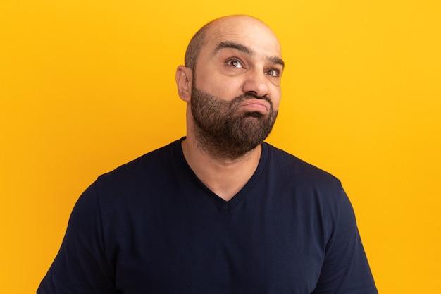 Uomo barbuto in maglietta blu scuro che osserva in su in piedi perplesso sopra la parete arancione