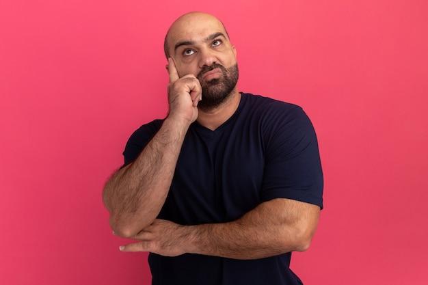Uomo barbuto in maglietta blu scuro che osserva in su in piedi perplesso sopra il muro rosa