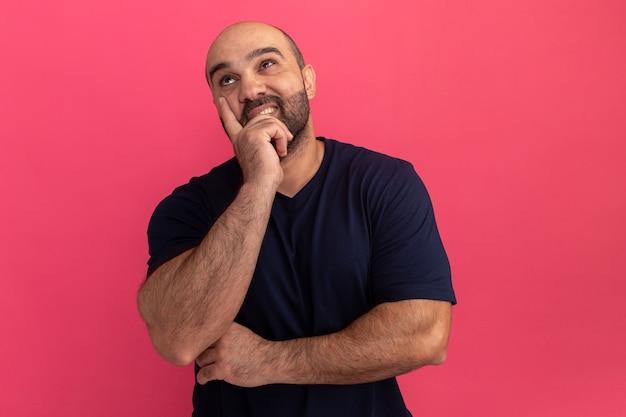 Uomo barbuto in maglietta blu scuro che osserva in su perplesso con la mano sul mento in piedi sopra il muro rosa