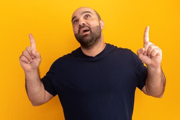 Uomo barbuto in maglietta blu scuro alzando lo sguardo sorpreso indicando con le dita indice in piedi sopra la parete arancione