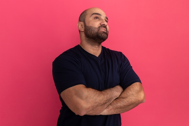 Uomo barbuto in maglietta blu scuro che osserva in su con espressione pensierosa seria con le braccia incrociate in piedi sopra il muro rosa
