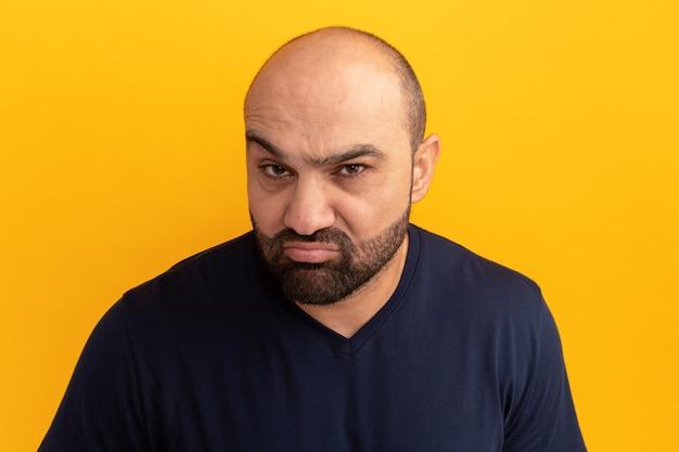 Uomo barbuto in maglietta blu scuro che fa la bocca ironica con espressione delusa in piedi sopra la parete arancione
