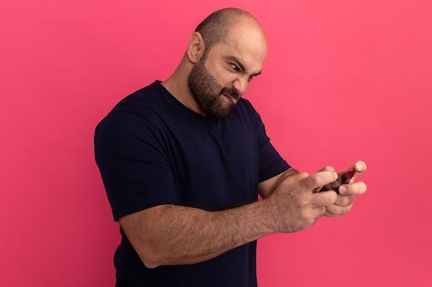 Uomo barbuto in maglietta blu scuro utilizzando smartphone che gioca giochi guardando infastidito ed eccitato in piedi sopra il muro rosa
