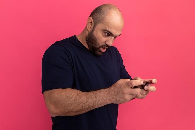 Uomo barbuto in maglietta blu scuro utilizza lo smartphone che gioca giochi guardando sorpreso e confuso in piedi sopra il muro rosa