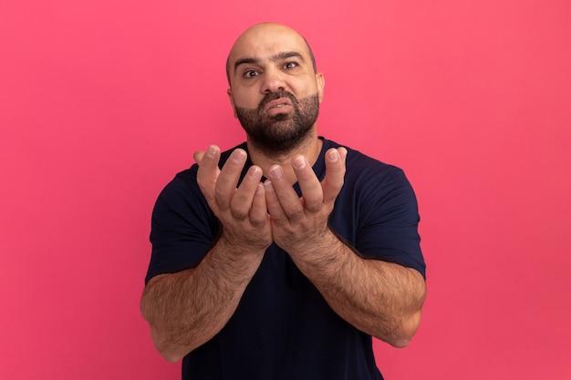 Uomo barbuto in maglietta blu scuro con le braccia alzate elemosinando con espressione di speranza in piedi sopra il muro rosa