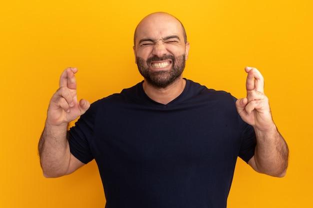 Uomo barbuto in maglietta blu scuro con gli occhi chiusi che esprime desiderio incrociare le dita in piedi sopra la parete arancione
