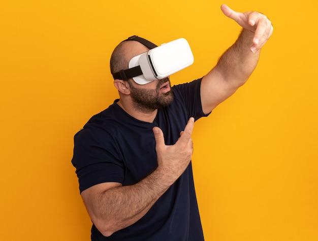Uomo barbuto in maglietta blu scuro con occhiali di realtà virtuale che gesticola con le mani davanti a lui in piedi sopra la parete arancione