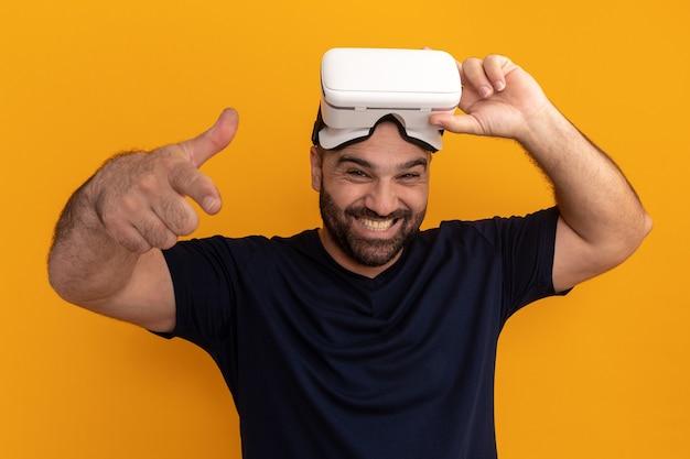 Uomo barbuto in maglietta blu scuro con occhiali di realtà virtuale felice ed emozionato che punta con il dito indice in piedi sopra la parete arancione