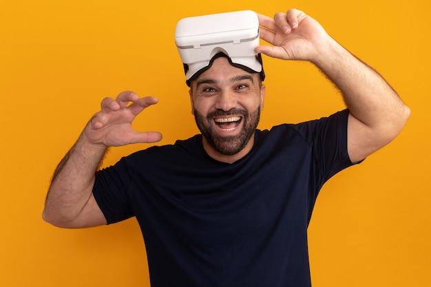 Uomo barbuto in maglietta blu scuro con occhiali di realtà virtuale sorridente allegramente con il braccio alzato in piedi sopra la parete arancione