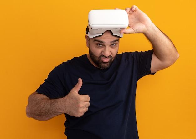 Uomo barbuto in maglietta blu scuro con bicchieri di realtà virtuale sorridente che mostra i pollici in su in piedi sopra la parete arancione
