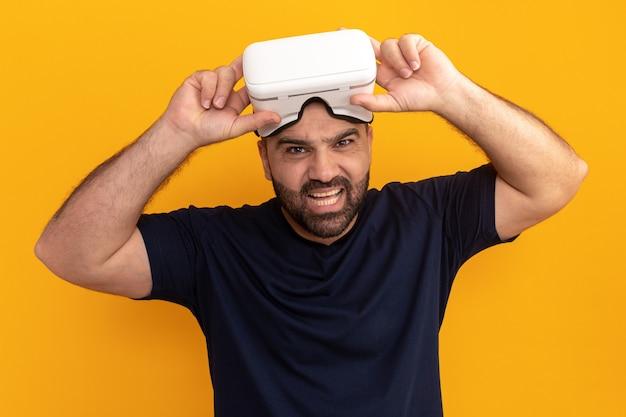 Uomo barbuto in maglietta blu scuro con occhiali di realtà virtuale con espressione infastidita in piedi sopra la parete arancione