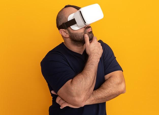 Uomo barbuto in maglietta blu scuro con occhiali di realtà virtuale con espressione pensierosa con la mano sul mento in piedi sopra la parete arancione