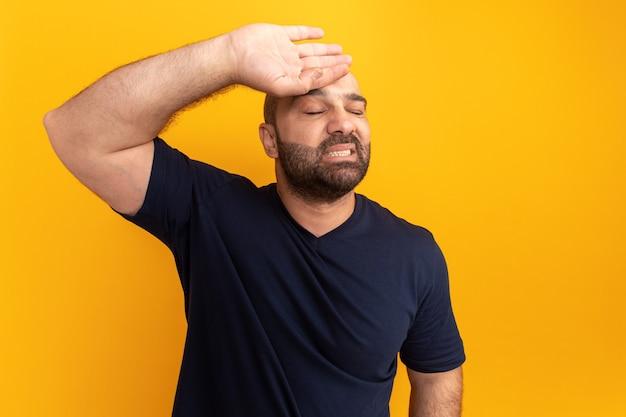 Uomo barbuto in maglietta blu scuro con la mano sulla fronte con espressione infastidita in piedi sopra il muro arancione
