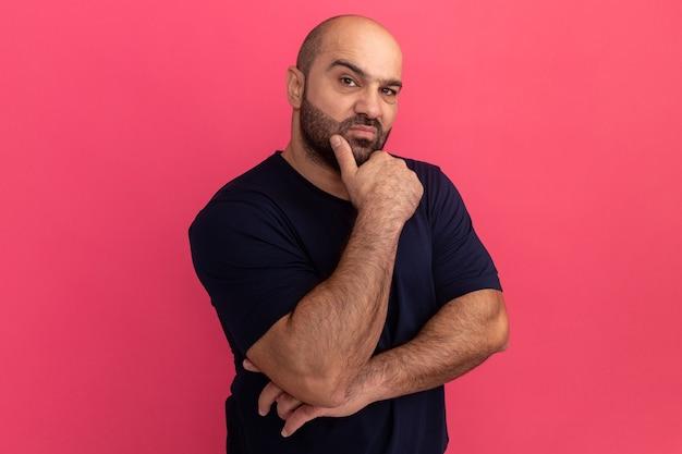 Uomo barbuto in maglietta blu scuro con espressione pensierosa con la mano sul mento in piedi sopra il muro rosa