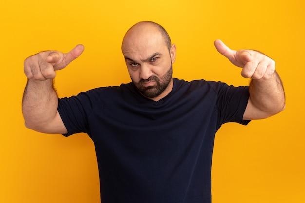 Uomo barbuto in maglietta blu scuro con viso serio rivolto con le dita indice in piedi sopra la parete arancione