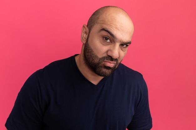 Uomo barbuto in maglietta blu scuro con seria faccia scettica in piedi sopra il muro rosa