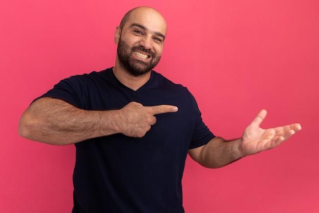 Uomo barbuto in maglietta blu scuro con il sorriso sul viso che presenta lo spazio della copia con il braccio rivolto con il dito indice verso il lato in piedi sopra il muro rosa