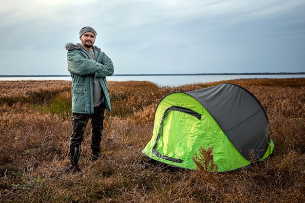 A bearded man near a camping tent in green  nature and the lake.  travel, tourism, camping.