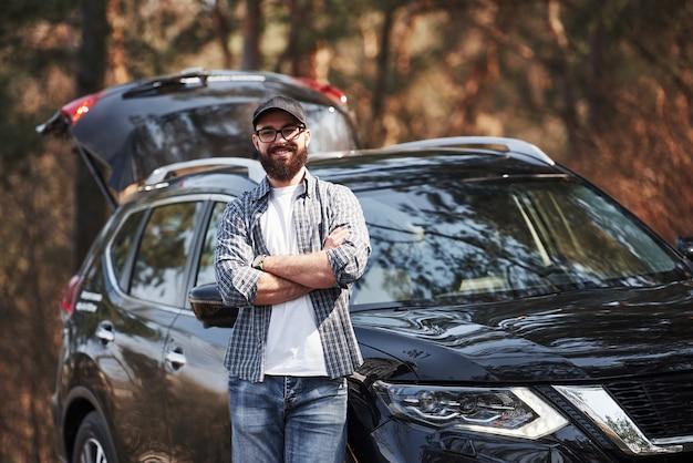 森の中の彼の真新しい黒い車の近くのひげを生やした男。休暇の概念