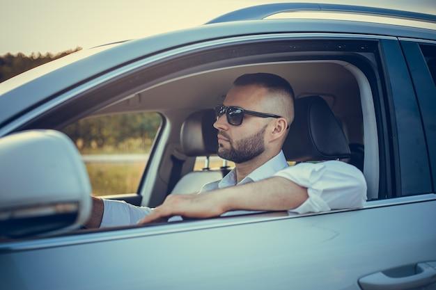 スタイルとステータスのひげを生やした男。白い車を運転しながら笑顔のフルスーツのハンサムな若い男。