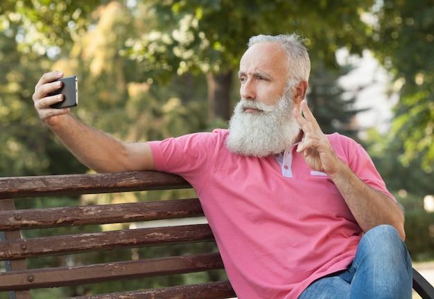 Selfieを取ってベンチにひげを生やした男
