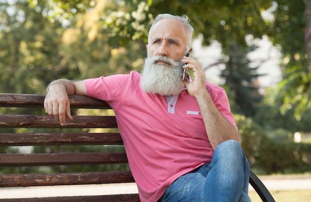 電話で話しているベンチのひげを生やした男