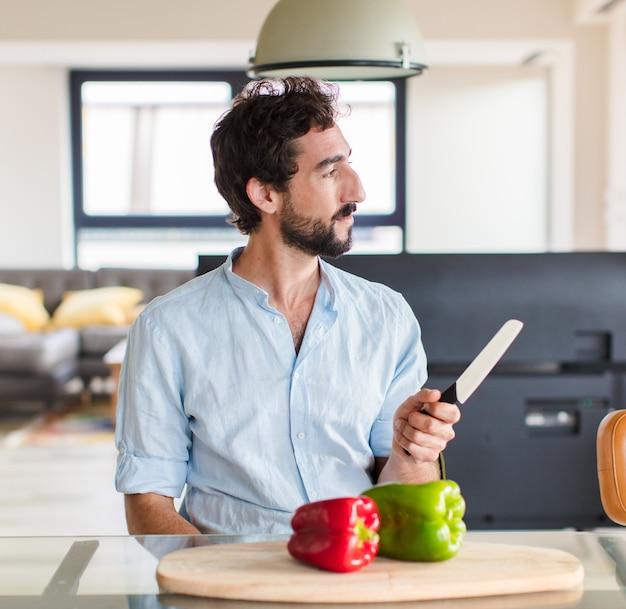 Бородатый мужчина в профиль смотрит, чтобы скопировать пространство впереди, думает, воображает или мечтает