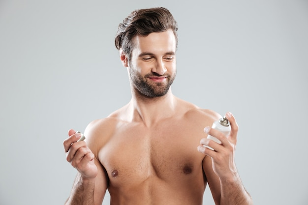 Bearded man opening perfume and smiling