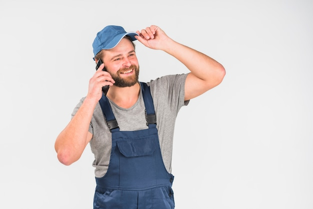 Bearded man in overall talking by phone