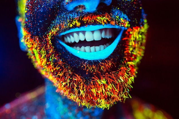 Bearded man painted in fluorescent powder