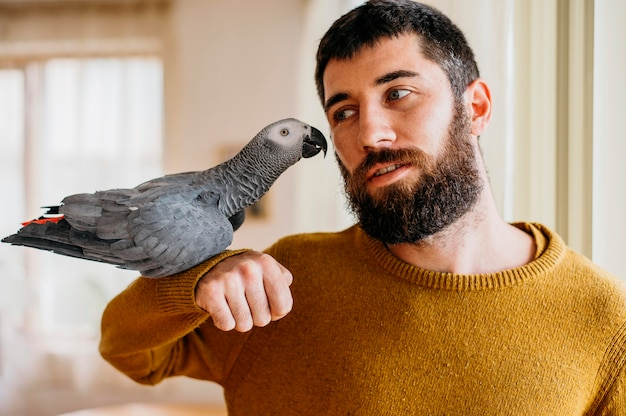 Бородатый мужчина ласкает милую птицу