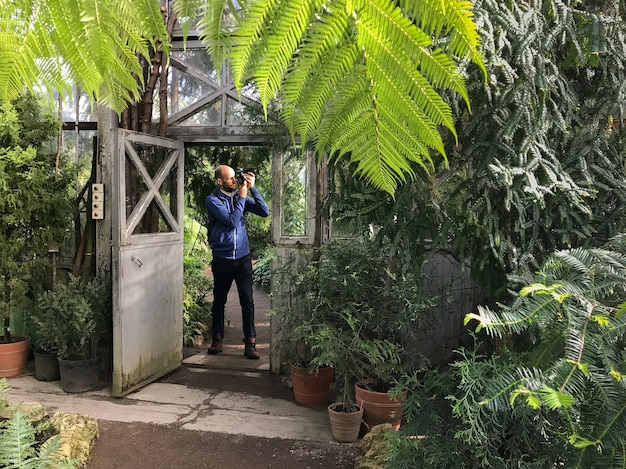 Bearded man photographer taking a photo at camera in greenhouse, standing with open old steel door on a sunny day.