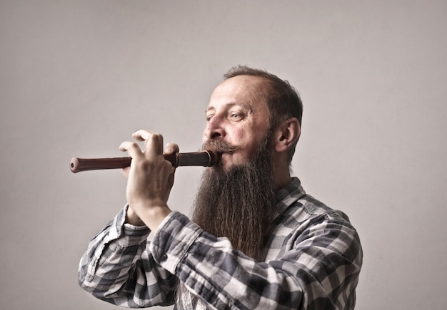 Bearded man playing on a flute