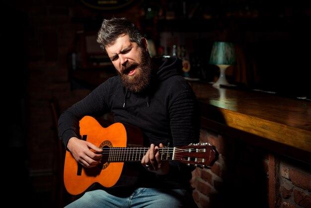 Бородатый мужчина играет на гитаре в пабе