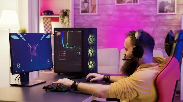 수염난 남자는 자신의 pc에서 온라인 비디오 게임을 하고 다른 플레이어와 이야기합니다. 방에 화려한 네온입니다.