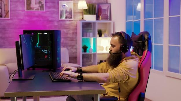화려한 네온이 있는 방에서 비디오 게임을 하는 수염 난 남자. 비디오 게임을 하면서 친구들과 이야기하는 남자.