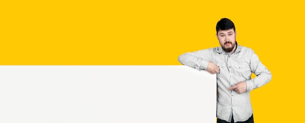 Bearded man pointing at banner with place for text, concept space for your advertisement, panoramic image