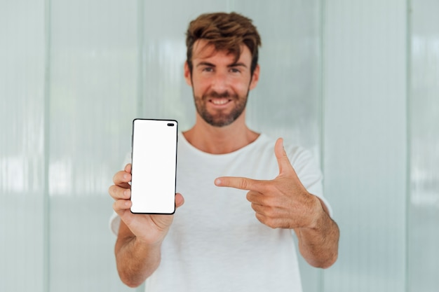 Bearded man pointing finger at phone